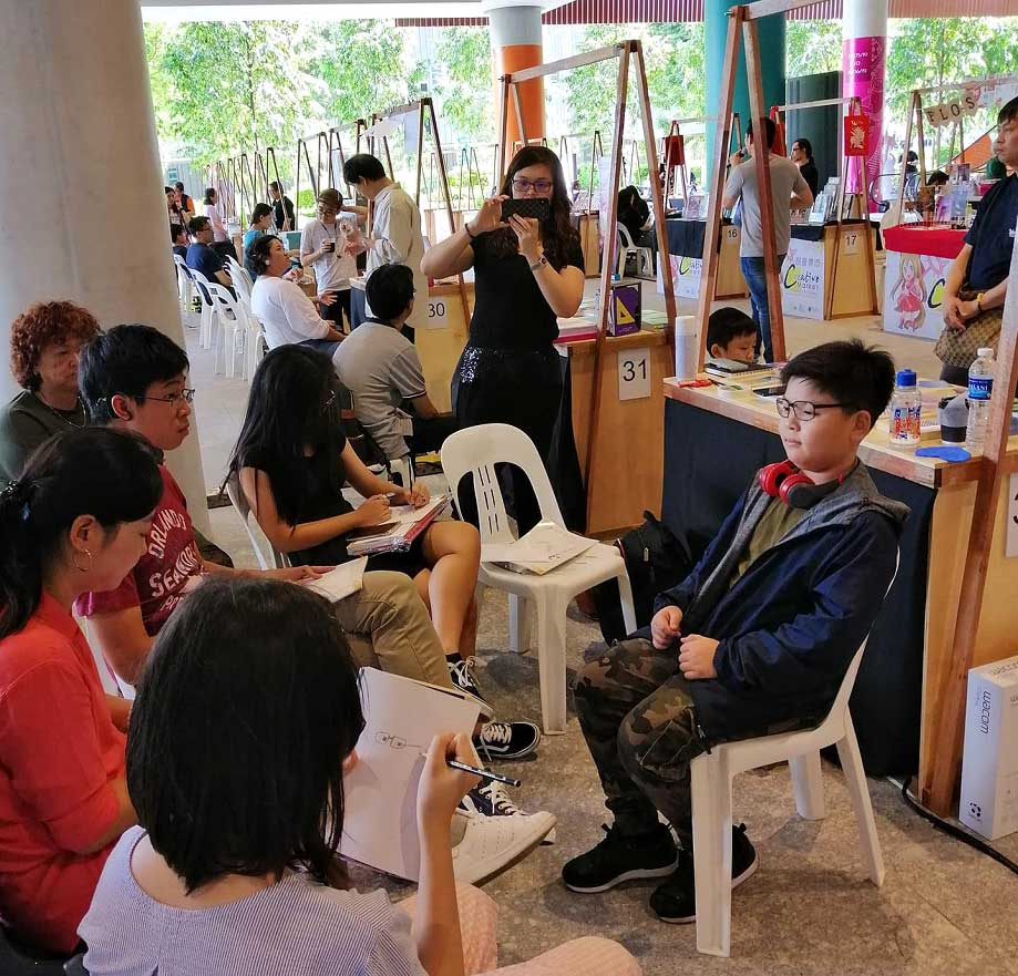 Booth exhibitors interacting with customers.